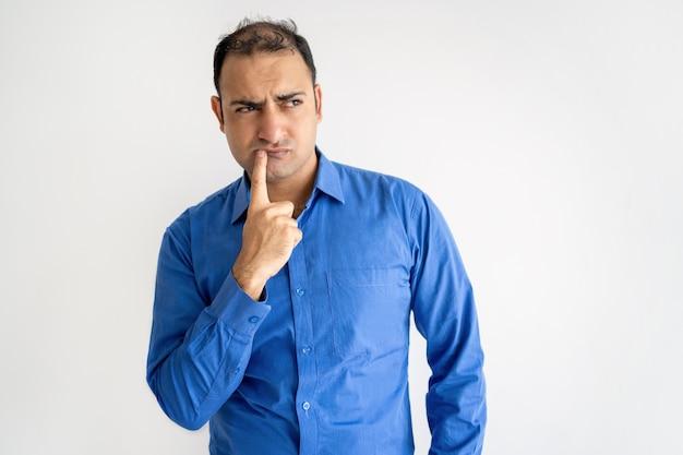 Pensativo homem indiano tocando os lábios e olhando para longe