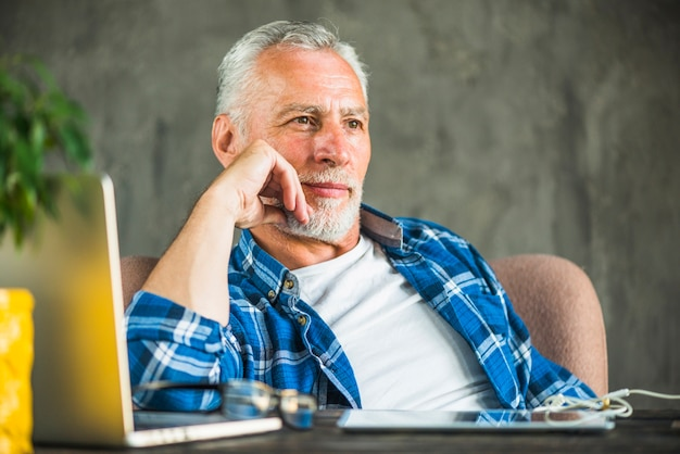 Pensativo homem sênior com laptop e tablet digital na mesa de madeira