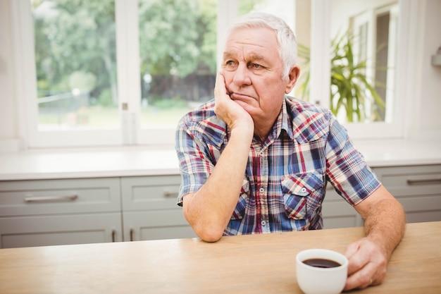 Pensativo homem sênior sentado à mesa com uma xícara de café