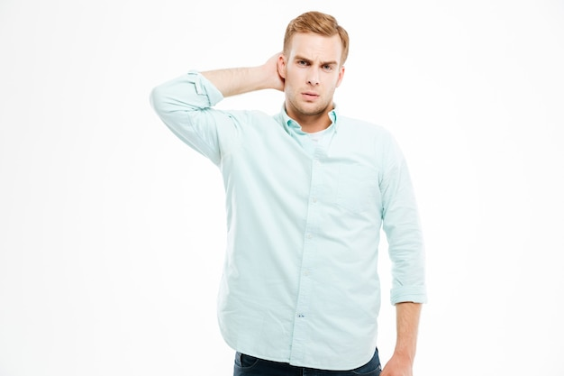 Pensativo jovem bonito de camisa branca pensando e