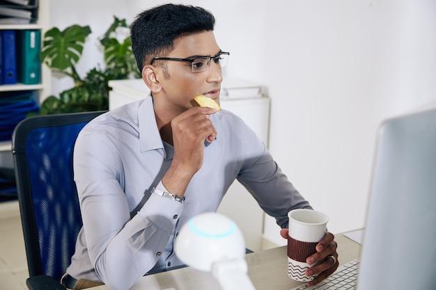 Pensativo, jovem desenvolvedor indiano de software de óculos, bebendo café, comendo biscoitos e verificando o código de programação na tela do computador