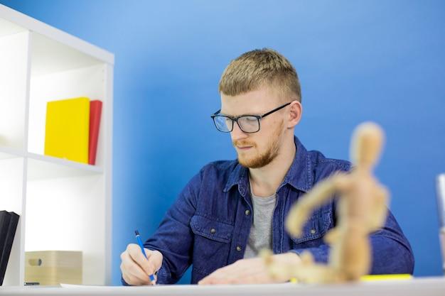 Pensativo jovem designer focado desenha com lápis com boneco de madeira