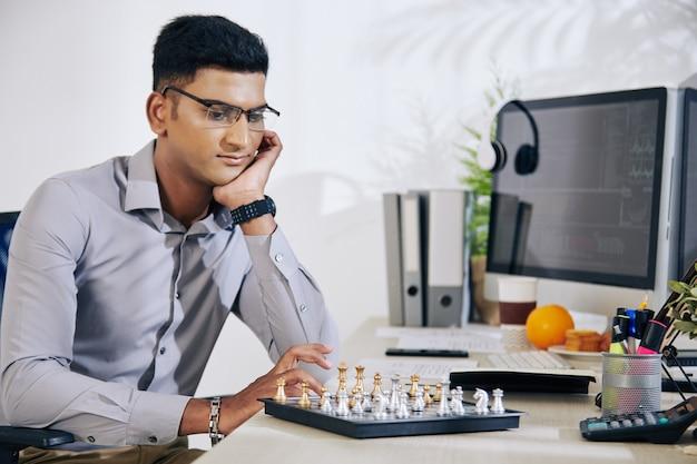 Pensativo jovem e bonito desenvolvedor indiano de software olhando para o tabuleiro de xadrez e pensando no próximo movimento