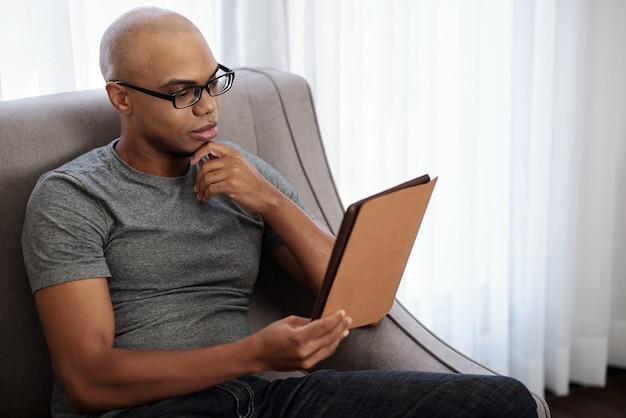 Pensativo, jovem e careca homem negro de óculos, sentado em uma poltrona e lendo um livro interessante no computador tablet