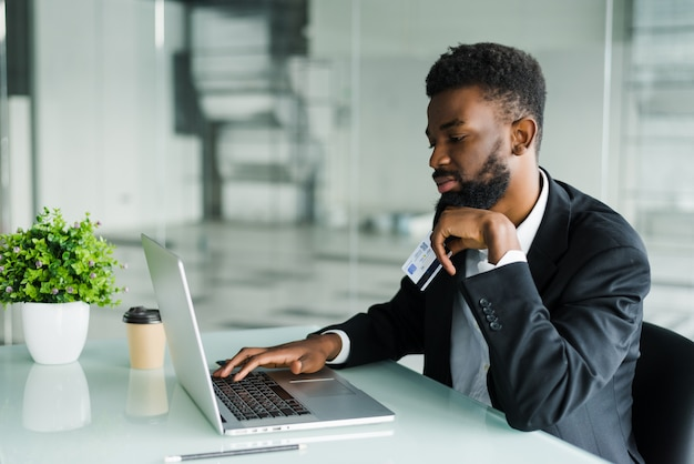 Pensativo jovem empresário americano africano trabalhando no laptop no escritório