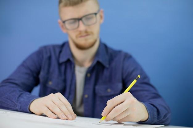 Pensativo jovem focado desenha com lápis isolado em fundo azul