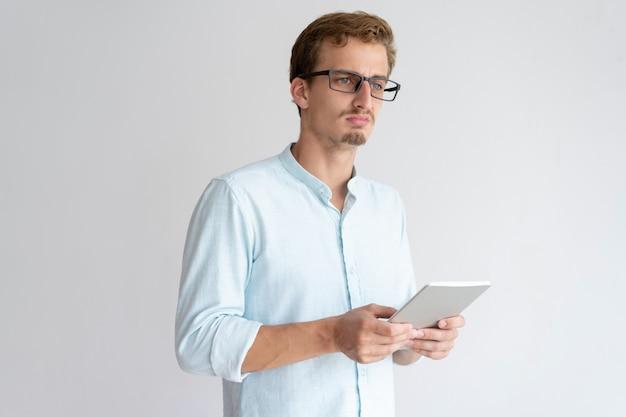 Pensativo jovem segurando o computador tablet