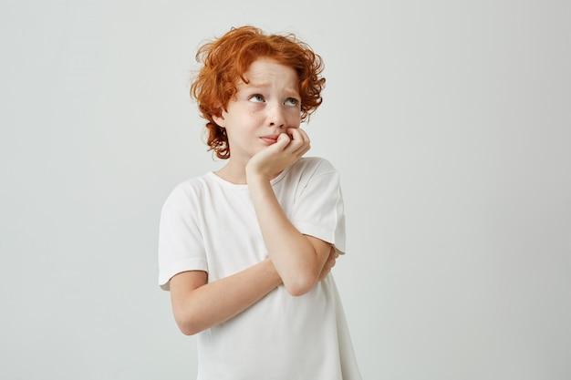 Pensativo lindo garoto ruivo, nervoso, olhando de lado, enquanto o professor de matemática tenta decidir quem responderá em perguntas difíceis.