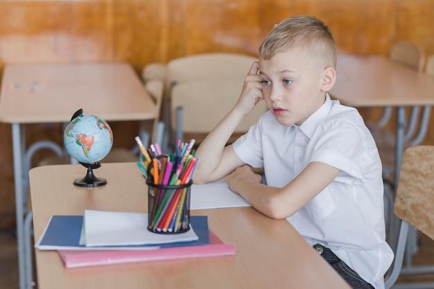 Pensativo, menino sentando, escrivaninha
