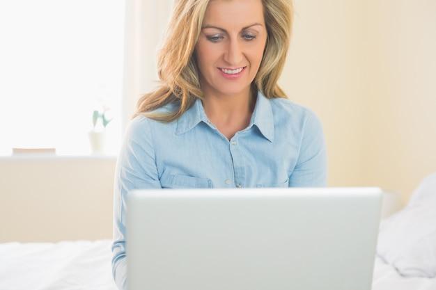 Pensativo, mulher, sentando, ligado, um, cama, usando, dela, laptop
