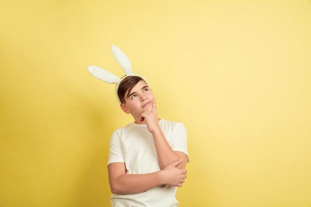 Pensativo, sonhando. menino caucasiano como um coelhinho da páscoa em fundo amarelo do estúdio. saudações de páscoa feliz. lindo modelo masculino. conceito de emoções humanas, expressão facial, feriados. copyspace.
