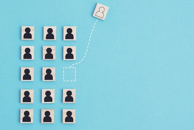 Pense diferente e conceito de líder. grupo de pessoas feito de blocos de madeira e um homem é movido para outra direção como pano de fundo de liderança de equipe