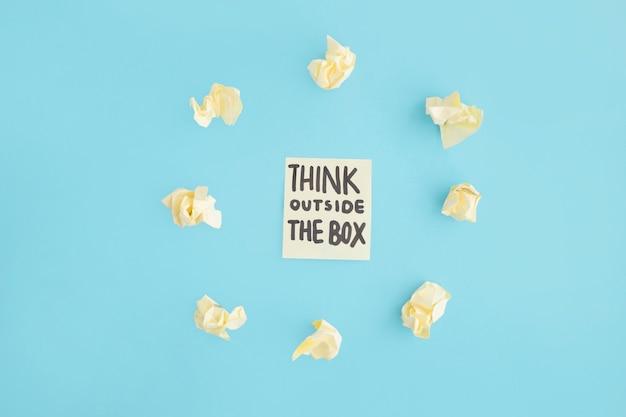 Pense fora do texto da caixa na nota adesiva rodeada de papel amassado amarelo sobre o pano de fundo azul