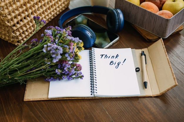 Pense grande frase motivacional no caderno aberto na mesa ao ar livre natureza morta com pense grande