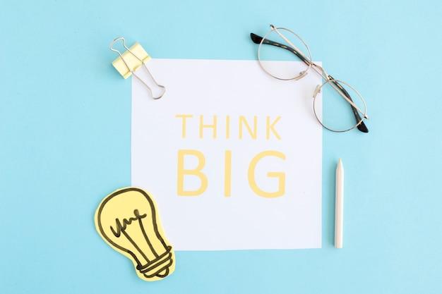 Pense grande texto em papel branco com lâmpada, óculos, pino de buldogue e lápis colorido sobre fundo azul