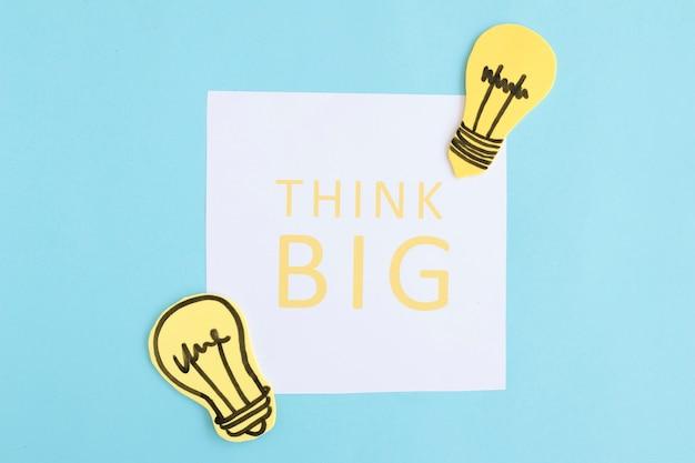 Pense grande texto em papel branco com lâmpadas em fundo azul