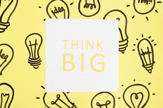 Pense grande texto na mão desenhada lâmpada sobre o fundo amarelo