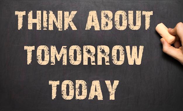 Pense no amanhã hoje! - mão feminina escrevendo texto no quadro-negro.