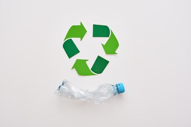 Pense no símbolo de reciclagem isolado da ecologia e amasse a garrafa de plástico