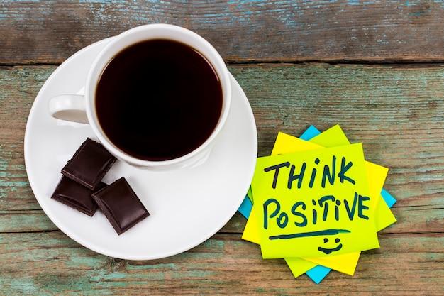 Pense positivo - caligrafia inspiradora em uma nota adesiva verde com uma xícara de café e um chocolate.