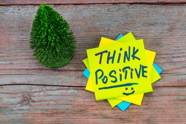 Pense positivo - caligrafia inspiradora em uma nota auto-adesiva verde e árvore de natal com fundo de madeira.