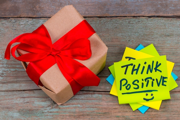Pense positivo - caligrafia inspiradora em uma nota auto-adesiva verde e um presente com fita vermelha em fundo de madeira.