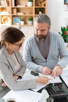 Pensionista barbudo apontando para documento financeiro enquanto consulta seu agente de seguros sobre seus pontos