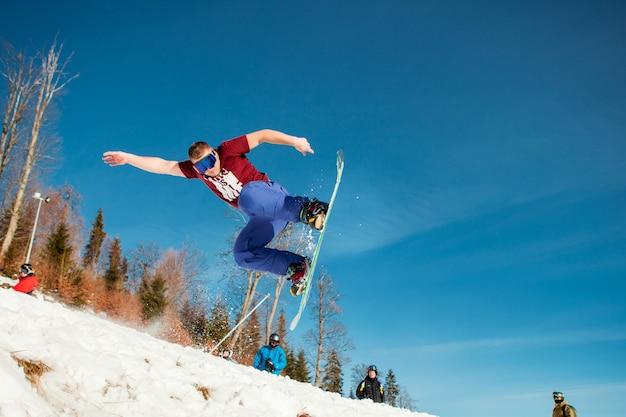 Pensionista de homem pulando em seu snowboard contra o pano de fundo das montanhas