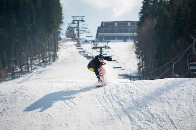 Pensionista feminina no snowboard depois de saltar sobre a encosta