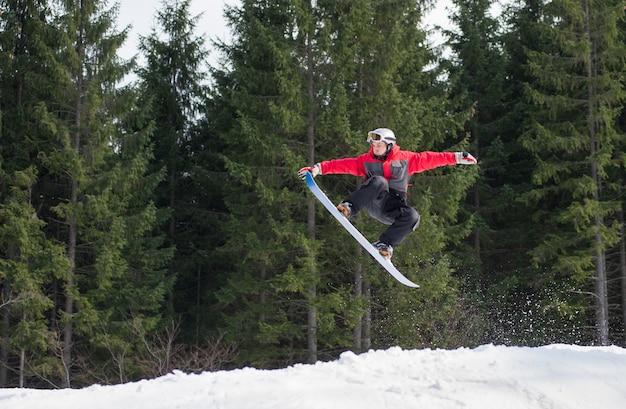 Pensionista masculina no snowboard saltando sobre a encosta
