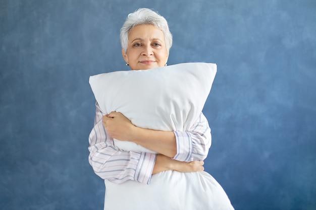 Pensionista posando e abraçando um travesseiro macio branco