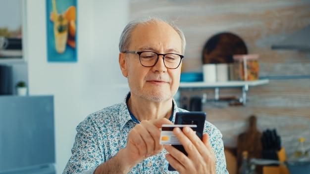 Pensionista que paga online usando cartão de crédito e aplicativo do smartphone durante o café da manhã na cozinha. idoso aposentado que usa o pagamento pela internet, compra do banco doméstico com tecnologia moderna