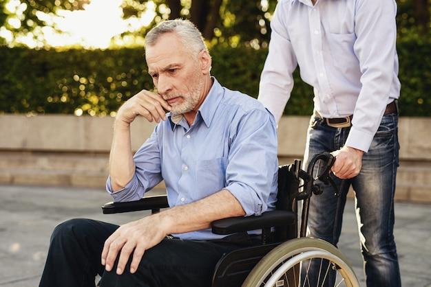 Pensionista triste em cadeira de rodas. preocupe-se com os deficientes.