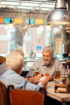Pensionistas alegres. aposentados alegres de cabelos grisalhos jogando cartas no bar juntos