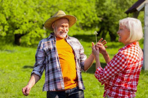 Pensionistas alegres. casal de aposentados se sentindo felizes depois de soprar no dente-de-leão