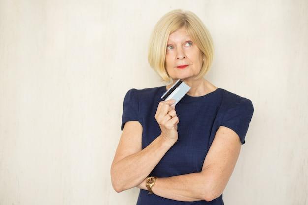 Pensive attractive senior lady holding cartão de crédito