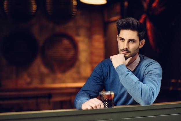 Pensive guy com penteado moderno perto de uma janela bebendo um refrigerante.