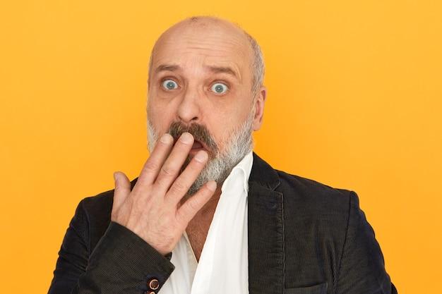 Penso engraçado, aposentado surpreso com barba espessa cobrindo a boca com a mão, recebendo más notícias inesperadas, tendo expressão facial intrigada de medo