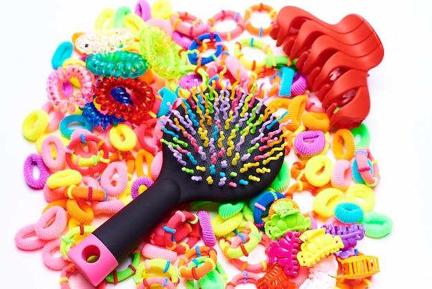 Pente colorido brilhante em elásticos coloridos para o cabelo em um fundo branco.