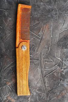 Pente de madeira dobrável em uma parede preta.
