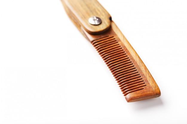 Pente de madeira feito de sândalo natural para homens em uma parede branca.