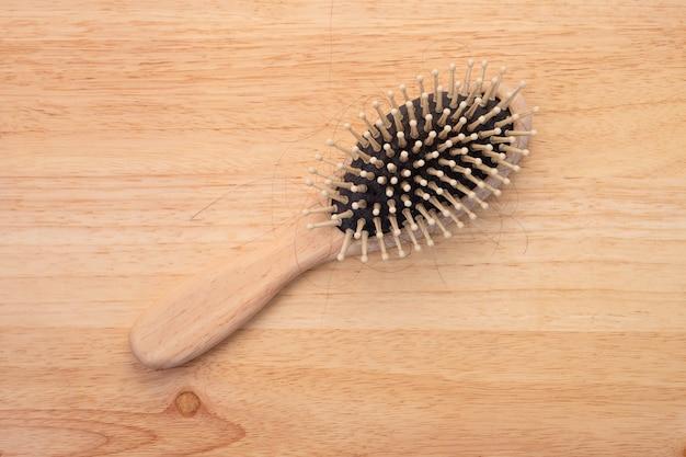 Pente de madeira na mesa de madeira, penteado a perda de cabelo, caspa, problemas de saúde.
