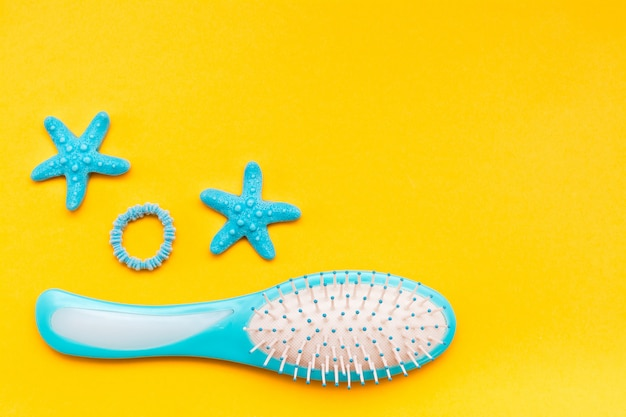 Pente de massagem, faixa de cabelo e grampo de cabelo em uma vista superior amarela