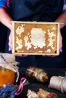 Pente de mel com mel. uma mulher detém o favo de mel em um fundo escuro.