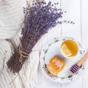 Pente de mel em um prato com as cores de lavanda e chá com limão