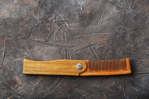 Pente de sândalo de madeira em uma parede texturizada preta.