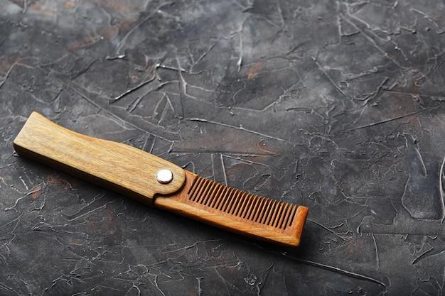 Pente de sândalo de madeira no preto texturizado.