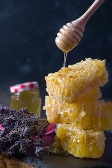 Pente do mel com flores de lavanda - comida doce em fundo escuro