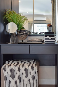 Penteadeira de madeira preta com cadeira marrom e acessórios em casa