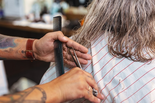 Penteado correto. barbeiro profissional usando instrumentos